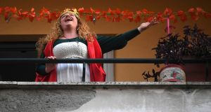A woman sings from her balcony in Rome. Photograph: Reuters