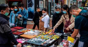 People wearing face masks look at electronic accessories for sale from a street vendor in the Causeway Bay district of Hong Kong. Photograph: Isaac Lawrence/AFP via Getty Images