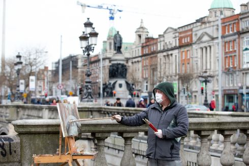 Artist John Paul pictured painting on O'Connell Bridge, Dublin. Photograph: Tom Honan