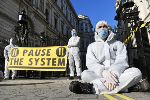 Protesters from a group called 'Pause the System' wear hazmat suits outside Downing Street in London. The group are calling for greater action from the government as the UK's coronavirus death toll rose to 35 on Sunday. Photograph: Dominic Lipinski/PA Wire