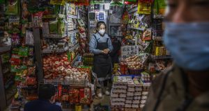 A Chinese shopkeeper waits for customers at a local market in Beijing on March 4th. A 55-year-old individual from Hubei province may have been the first person to have contracted Covid-19 in November last year. Photograph: Getty Images