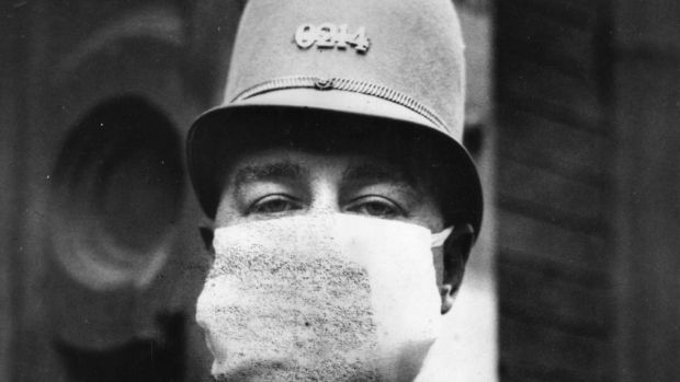 An American policeman wearing a flu mask in 1918 to protect himself from Spanish flu: we are all looking for our own comforting Mixture. Photograph: Topical Press Agency/Getty