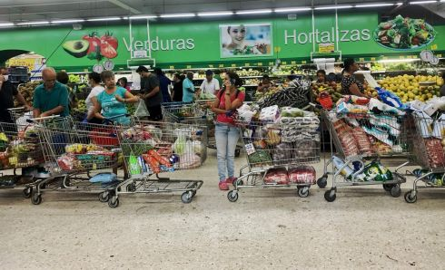 COLOMBIA: People queue with full carts at a supermarket in Cali, Colombia. Photograph: Luis Robayo/AFP via Getty Images