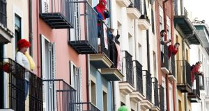 Residents in the old quarter of Pamplona, northern Spain, hold a  fancy-dress event on their balconies on Thursday, as Spain goes into its fiftd day of lockdown to contain the spread of the Covid-19 pandemic. Photograph: Jesus Diges/EPA