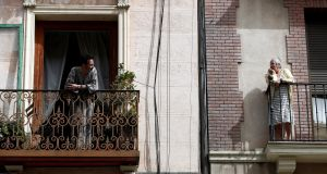 Two neighbours chat from their balconies  in Madrid on Thursday as Spain faces its fifth day of lockdown to contain the spreading Covid-19 outbreak. Photograph: Mariscal/EPA