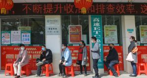 China presents itself as a lesson in how states can push back the deadly virus. Customers lining up to have their temperature taken before entering a bank in  China's central Hubei province.  Photograph:   STR/AFP via Getty Images