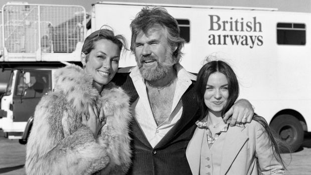 Kenny Rogers at London's Heathrow airport in 1977 with his wife of a few weeks, television star Marianne Gordon (left) and singer Crystal Gayle. Photograph: PA Wire