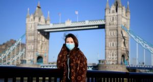 A woman wears a protective mask  in front of Tower Bridge  in London. There have now been 5,683 diagnosed cases in the UK and 281 deaths. Photograph: Alex Davidson/Getty