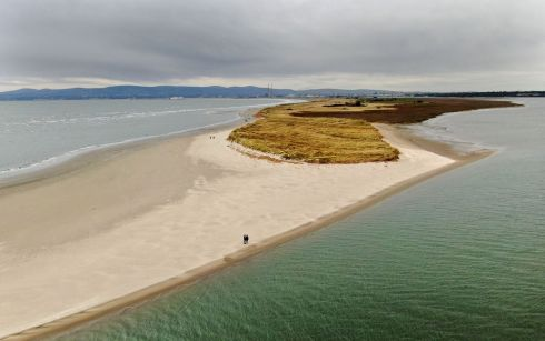 SO NEAR, SO FAR: Walkers exploit the quiet of the sandbar on Bull Island as they find themselves in splendid isolation, quite close to Dublin city centre, amid the coronavirus outbreak. Photograph: Alan Betson