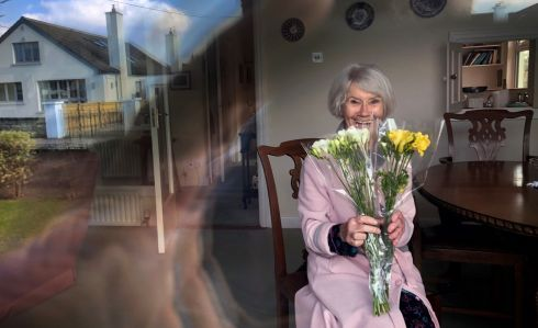 "FRESH FRESIAS FOR MUM: Ellen Creed, of Dublin, with a bunch of flowers that was left outside her door, due to coronavirus ""cocooning"" of older persons, on Mother's Day. Photograph: Bryan O'Brien"