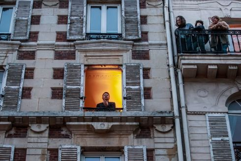 SPLENDID ISOLATION: Tenor Stephane Senechal sings at his window for other residents on their street in Paris. Mr Senechal sings every evening since the beginning of containment measures to lock down France in an attempt to stop the spread of coronavirus. Photograph: Christophe Petit Tesson/EPA