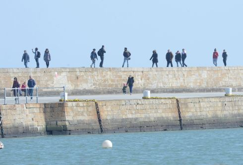 WALKING ON WALLS: Walking the pier at Howth on Sunday, with most people observing social distancing due to coronavirus. Photograph: Alan Betson