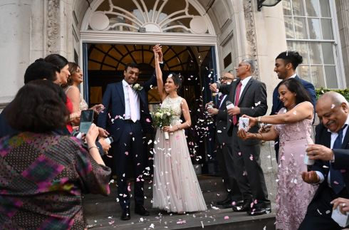 LIFE GOES ON: Shray Patel (left) and bride Sheena Patel  have confetti thrown on them by guests after marrying at Chelsea Town Hall in London, Britain, despite restrictions imposed due to coronavirus. Photograph: Neil Hall/EPA