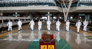 Staff members spray disinfectant at Wuhan Railway Station in Wuhan in China's central Hubei province. Photograph:  STR/AFP via Getty Images