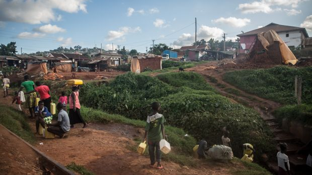 Residents of Namuwongo, Kampala, gather to carry water from a well. Most homes have no running water. Photograph: Sally Hayden