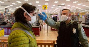 A customer has her temperature checked at the entrance of a supermarket in Milan, Italy, on Tuesday. Photograph: Marco Ottico/EPA