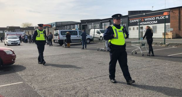 Gardaí observe a socially distanced queue in the car park at the Woodie's store in Glasnevin, Dublin. Photograph: Alan Betson