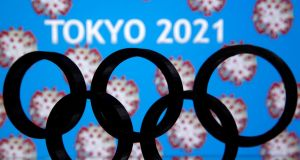 "A 3D printed Olympics logo is seen in front of a display for ""Tokyo 2021"". Photograph:  Dado Ruvic/Reuters"