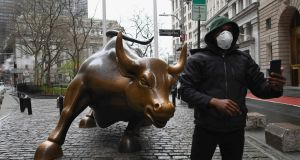 A man wearing a face mask takes a selfie at the Charging Bull statue near the New Stock Exchange. Photograph: Angela Weiss/AFP