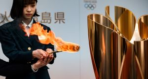 The Olympic flame is displayed outside Fukushima railway station. Tokyo 2020 is postponed until 2021, but will still be called Tokyo 2020. Photograph: Philip Fong/AFP