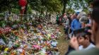 A file image showing people looking at  ributes left in Christchurch, New Zealand, after the mosque shootings in 2019. The Australian man accused of killing 51 worshippers  changed his plea to guilty on Thursday.  Photograph: Getty Images