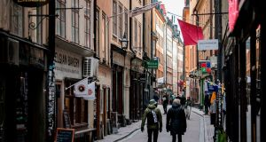 People walk in the main street of the old town in Stockholm, Sweden.  While the rest of Europe is in near-lockdown in a bid to curb the spread of the  Covid-19,  Sweden is taking a softer line. Photograph: AFP via Getty