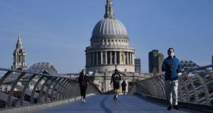 A jogger wears a mask as he runs along Millennium Bridge in London. Photograph:  Daniel Leal-Olivas/AFP via Getty Images