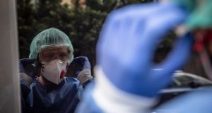 A medical professional adjusting his personal protective equipment  outside the home of a Covid-19-positive patient. Photographer: Bloomberg