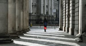 A pedestrian walks through an otherwise deserted College Green in Dublin. Photograph: Aidan Crawley/EPA