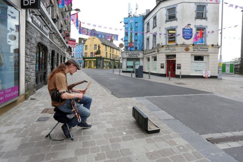 CAPITAL OF CULTURE: A busker performs on an empty Shop Street in Galway city. Photograph: Joe O'Shaughnessy