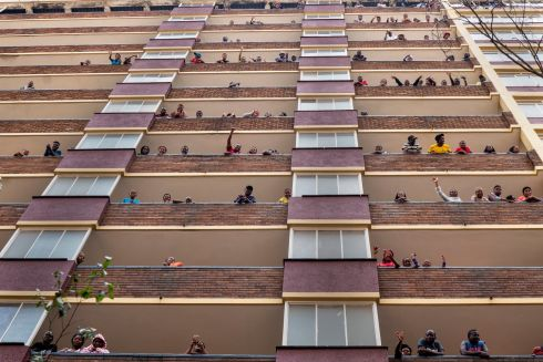 WAVE IN ISOLATION: Residents of the densely populated Hillbrow area of Johannesburg, South Africa, stand and wave from their balconies. The country is in a nationwide lockdown for 21 days in an effort to mitigate the spread of coronavirus. Photograph: Jerome Delay/EPA