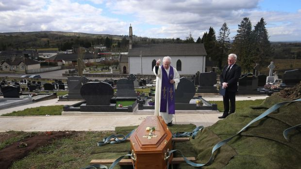 Fr Gerard Alwill blesses the coffin of Fermanagh's first Covid-19 victim Anne Best (72) at St Ninnidh's cemetery. Undertaker Pat Blake stands nearby. Ms Best's husband Tom had to stay away. Photograph: John McVitty