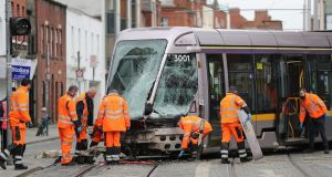 OFF THE RAILS: Workers investigate the aftermath of a since-removed truck colliding with a Luas tram at the junction of Queen Street and Benburb Street in Dublin city centre on Monday morning. The Luas driver sustained injuries described as non-life threatening. Photograph: Nick Bradshaw