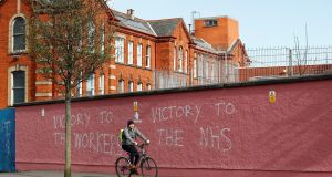 A cyclist passes in front of the Royal Victoria Hospital  in Belfast with graffiti supporting the NHS. Photograph:  Jason Cairnduff/Reuters