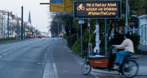A man rides a cargo bike next to a sign reading 'Riding to work by bike avoids an infection – #FlattenTheCurve' in Berlin. Photograph: Alexander Becher/EPA
