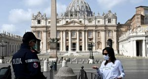 A policeman talks with a woman in front of an empty St Peter's Square prior to Pope Francis' livestreamed Angelus prayer on March 29th. Photograph: AFP