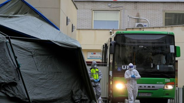 A member of the UME (Emergency Army Unit) wearing a protective suit stands next to a bus carrying Covid-19 patients waiting to be transported to a temporary hospital set up at the IFEMA convention centre in Madrid, Spain. Photograph: AP