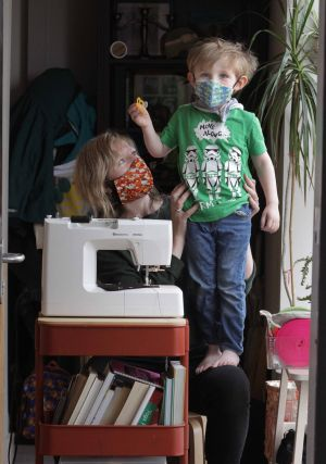 ALL SEWN UP: Textile printer Liz Walsh, with her three-year-old son Tadhg Jackson, has been making protective masks at home in Dublin since her linen studio, 29 Bride Street, shut its door on March 12th. Photograph: Mark Stedman