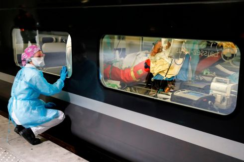 GOODBYE FOR NOW: A healthcare worker watches from a platform of the Gare d'Austerlitz train station in Paris through the window of a medicalised TGV high speed train before its departure to evacuate patients infected with coronavirus from Paris hospitals to other hospitals in the Brittany region. Photograph: Thomas Samson/AFP via Getty Images