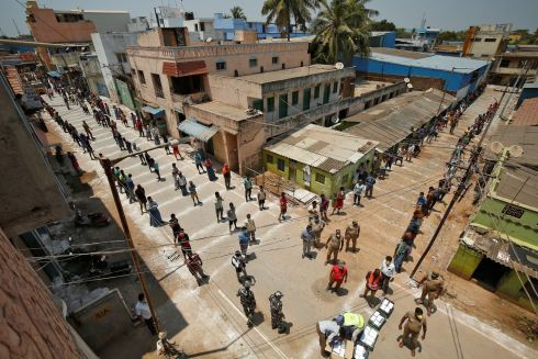 INDIA: People stand on the lines drawn to maintain safe distance as they wait to receive free food being distributed by Central Reserve Police Force during a 21-day nationwide lockdown in Chennai. Photograph: P Ravikumar/Reuters