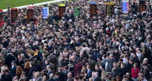 Racegoers attend the final day of the Cheltenham festival. Photograph:  Glyn Kirk/AFP via Getty Images