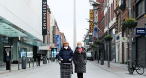 Two women wearing face masks make their way to the shops on an almost deserted Henry Street in Dublin's city centre. Photograph:  Brian Lawless/PA Wire