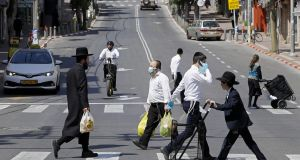 Ultra-Orthodox Jews, some wearing masks, cross a street with their shopping in the religious Israeli city of Bnei Brak, near Tel Aviv, on Friday. Photograph: Jack Guez/AFP via Getty Images