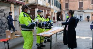 Municipal workers distribute masks and gloves at the Rialto market in Venice on Saturday, as new restrictions for open-air markets were implemented by the Veneto region to prevent the spread  of coronavirus. Photograph: Manuel Silvestri/Reuters