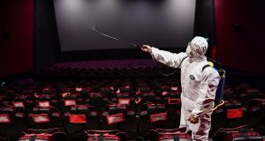 A cinema in Shenyang in China is sprayed with disinfectant as it prepared to reopen in March: all cinemas in China are now closed again. Photograph: STR/AFP via Getty Images.