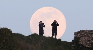A pink supermoon rises over the Rock of Dunamase in Co Laois on Tuesday evening. Photograph: Niall Carson/PA Wire