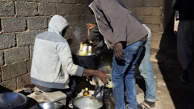 African migrants prepare food at a Safe House in the 'ghost city' of Bani Walid, on the edge of the desert 170km southeast of the Libyan capital Tripoli in 2017. Photograph: Mahmud Turkia/AFP via Getty Images