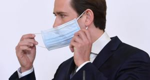 Austrian chancellor Sebastian Kurz takes off his face mask during a press conference on Monday in Vienna.  Photograph: Helmut Fohringer/APA/AFP via Getty Images