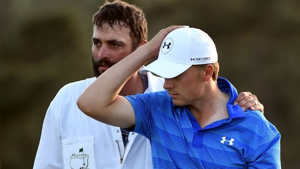 A dejected Jordan Spieth with caddie Michael Greller aafter finishing on the 18th green during the final round of the 2016 Masters at Augusta National. Photographer: Harry How/Getty Images