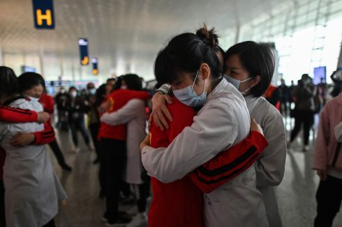A VIEW FROM WUHAN: Staff from Jilin province (in red) hug nurses from Wuhan after working together to tackle Covid-19, at Tianhe airport, China. Photograph: Hector Retamal/AFP via Getty Images